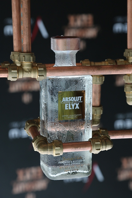 The Absolut Elyx bottle amidst copper pipes